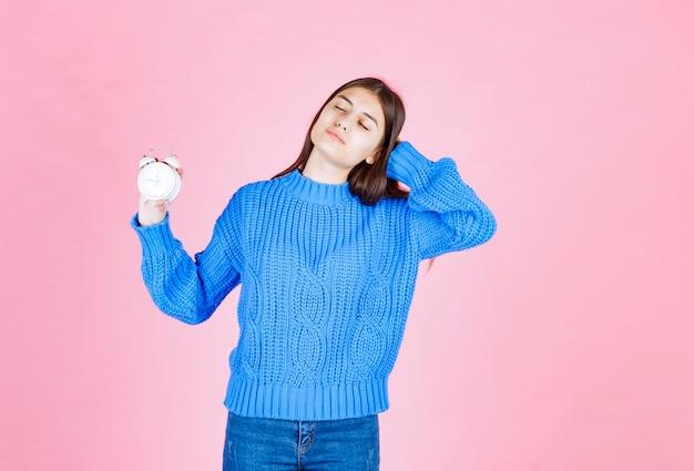 Ritratto di un modello di ragazza che tiene una sveglia sulla parete rosa.