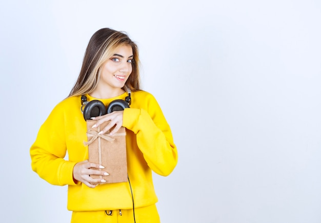 Ritratto di una modella che tiene in mano una scatola di carta con fiocco isolato su un muro bianco