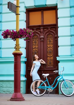 Portrait of girl near vintage door with retro bicycle, old building