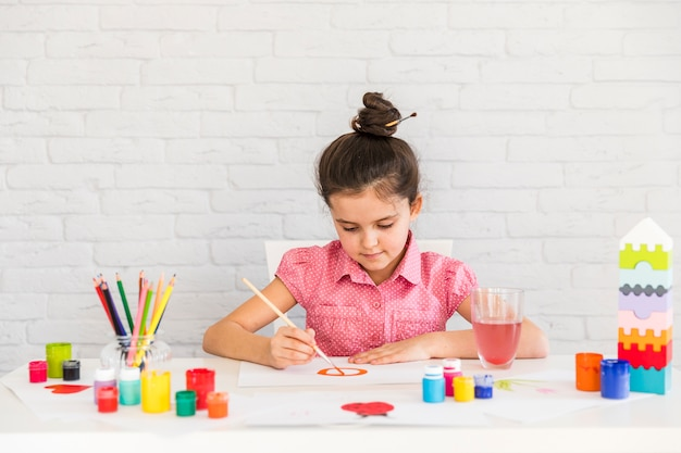 Portrait of a girl painting on white paper with paintbrush