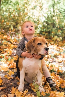 Portrait of girl playing with beagle dog in forest
