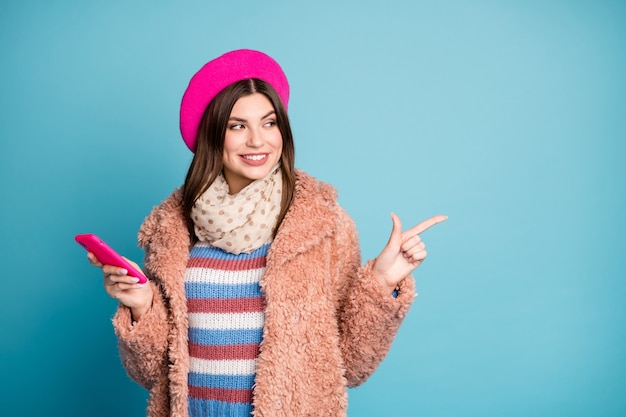 Portrait of girl pointing aside copy space advert hold phone