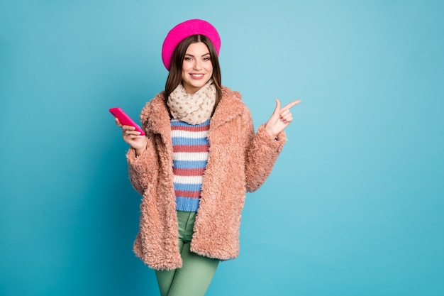 Portrait of girl pointing copy space hold phone