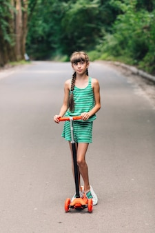 Portrait of a girl posing with kick scooter on street