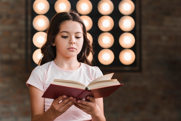 Portrait of girl reading book in front of stage light