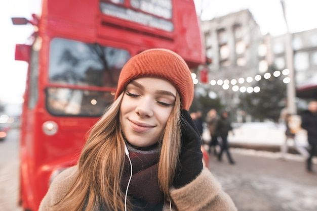 肖像画の女の子は都市景観の背景に音楽から喜びを受け取る