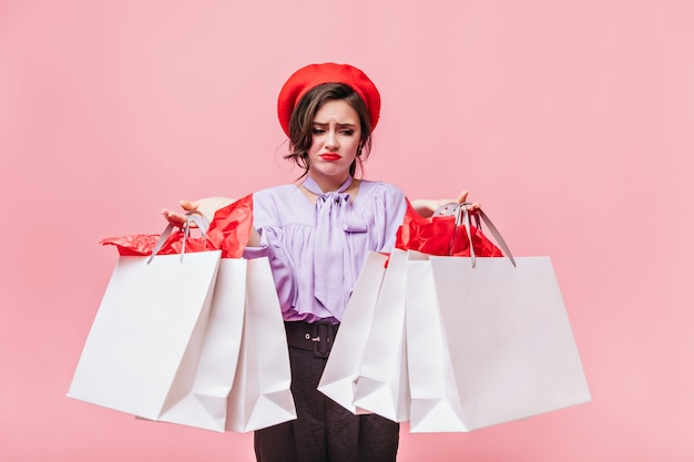 Portrait of girl in red beret looking disgruntled at packages with clothes. lady in lilac blouse and black pants posing on pink background.