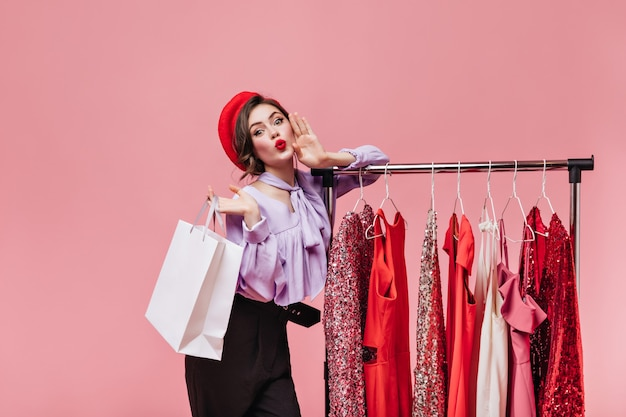 Ritratto di ragazza in berretto rosso fischiettando e tenendo il pacchetto su sfondo rosa con grucce con abiti.
