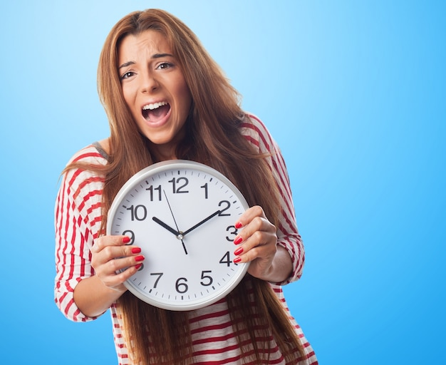 Portrait of girl screaming and holding clock