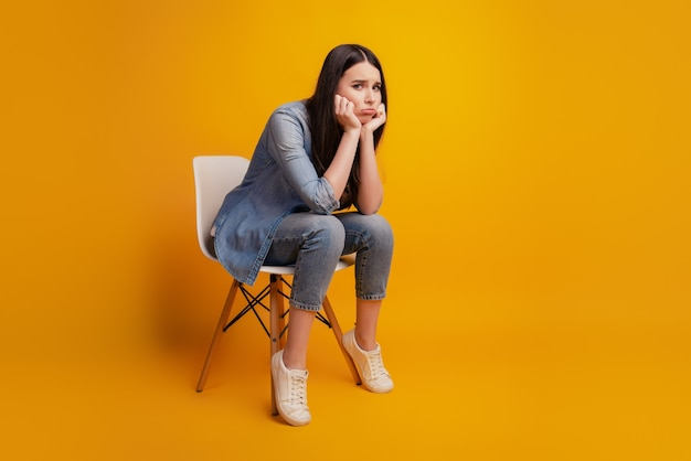 Portrait of girl sit chair unhappy face fists cheeks wear casual clothes on yellow background