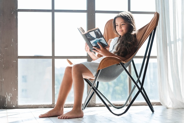 Portrait of a girl sitting on chair near the window reading book