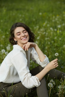 Portrait of a girl sitting in a field on spring grass among dandelion flowers.