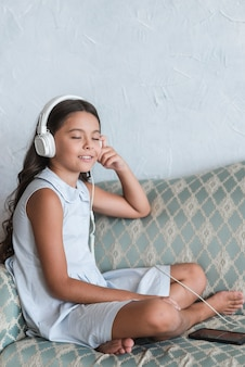 Portrait of a girl sitting on sofa enjoying the music on headphone attached to cell phone