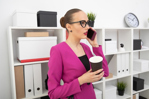 Portrait of a girl in a skirt and pink jacket who drinks coffee and talks on the phone
