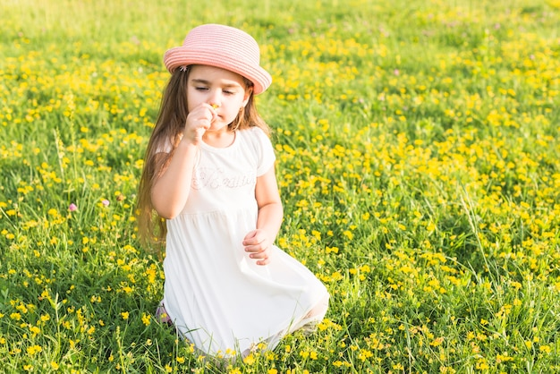 Portrait of girl smelling flower sitting in the meadow