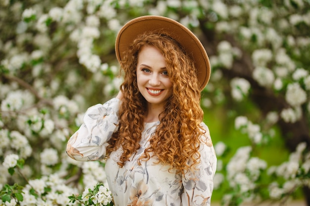 Portrait of a girl smiling and being happy on a bright sunny spring day. young woman with curly hair wearing white dress and beige hat feels satisfied walking in the blooming park. spring concept.