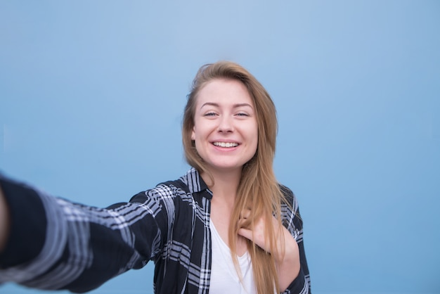 Portrait of a girl standing on a blue background and making her portrait on the camera.