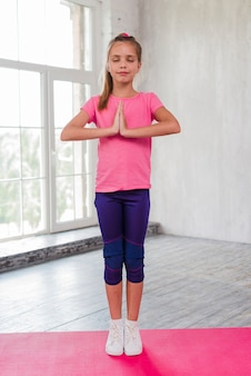 Portrait of a girl standing on exercise mat meditation