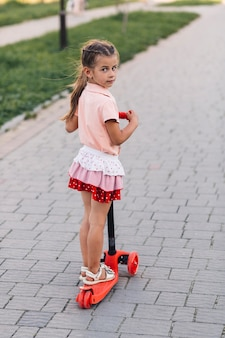 Portrait of a girl standing on red push scooter looking at camera
