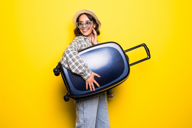 Portrait of a girl in straw hat and sunglasses with suitcase isolated over golden yellow wall