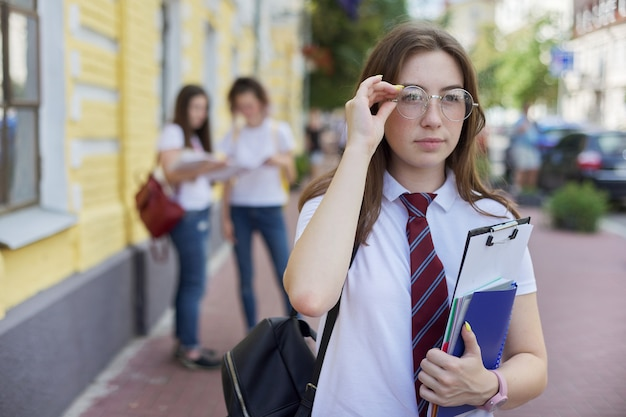 Portrait girl student teenager in glasses tie white t-shirt with backpack. background yellow brick building, group of students