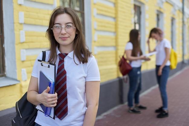 Подросток студента девушки портрета в очках связывает белую футболку с рюкзаком. фон желтого кирпичного здания, группа студентов