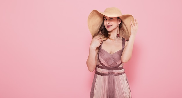 Portrait of a girl in a summer hat and dress on a pink wall
