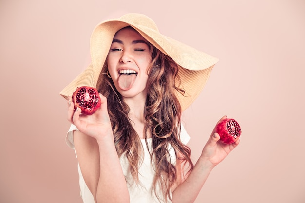 Portrait of a girl in a summer hat with fruit on a colored wall
