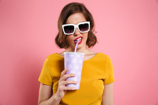 Portrait of a girl in sunglasses holding cup with drink