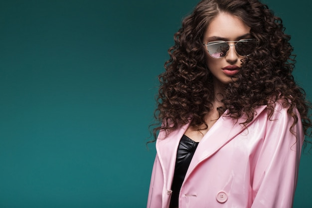 Portrait of a girl in sunglasses and a pink lacquer coat
