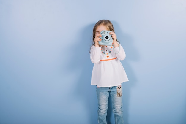 Portrait of a girl taking photograph with vintage instant camera standing against blue backdrop