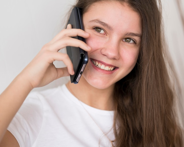 Ragazza del ritratto che parla sopra i telefoni