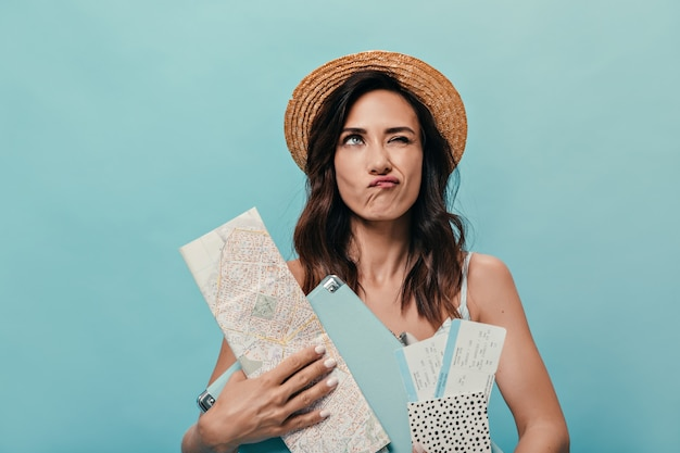 Portrait of girl thoughtfully posing on blue background with city map and suitcase. woman in straw hat with dark wavy hair.