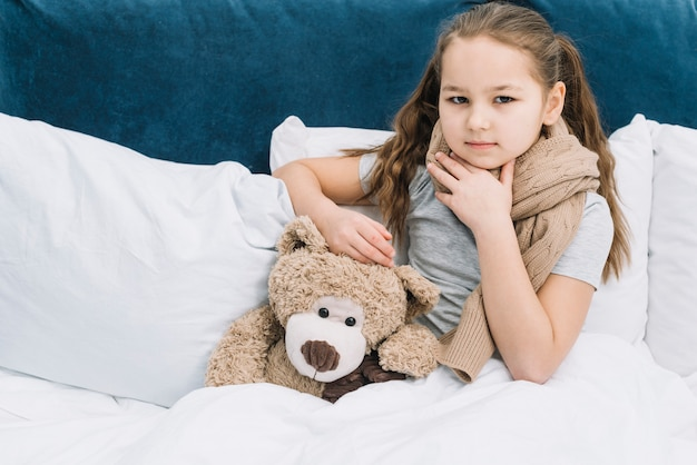 Portrait of a girl touching her neck with hand siting with teddy bear on bed
