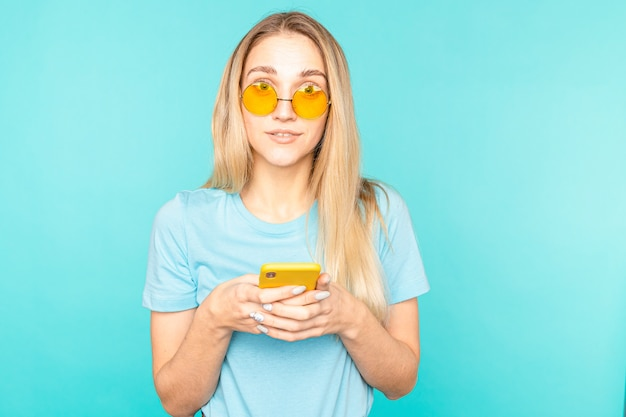 Portrait of girl use her smartphone read social media news scream wow omg isolated over blue color.