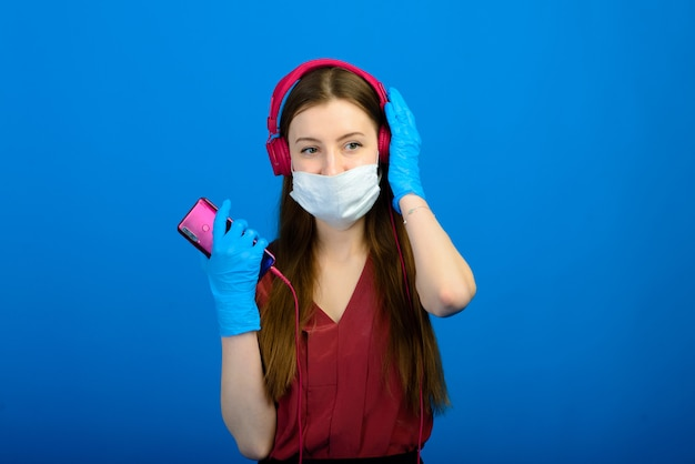 Portrait of a girl wearing a face mask on a blue background