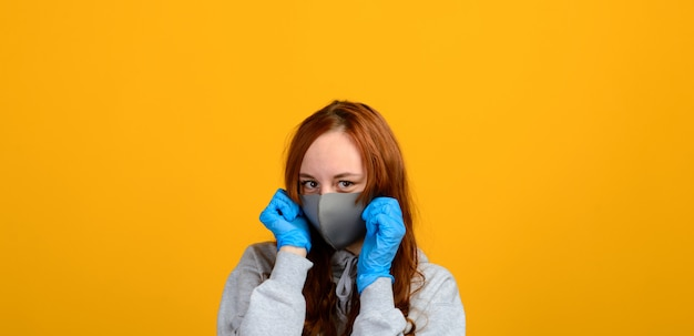 Portrait of a girl wearing a face mask on a yellow background