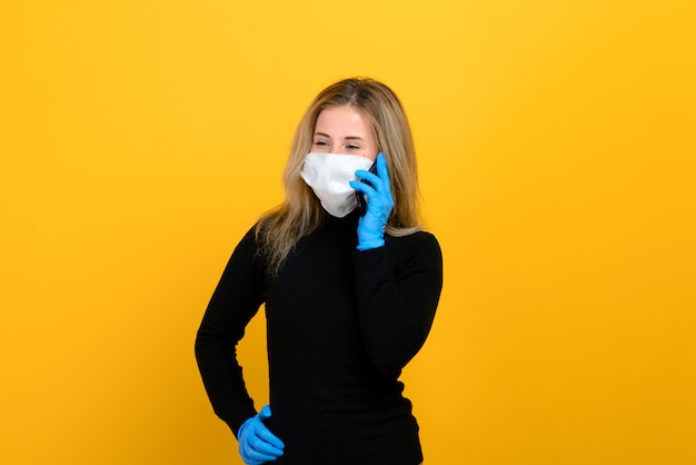 Portrait of a girl wearing a medical mask on a yellow background