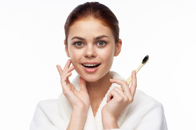 Portrait of a girl on a white background in a robe with a toothbrush in her hands