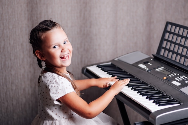 Portrait girl in a white dress learning to play an electronic synthesizer