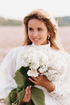 Portrait of a girl in a white dress with a bouquet of flowers in summer in nature in the field