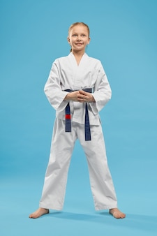 Portrait of girl in white kimono with blue belt in studio.