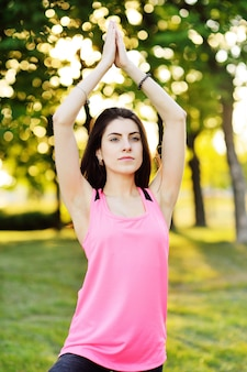 Portrait of a girl who does yoga on green grass