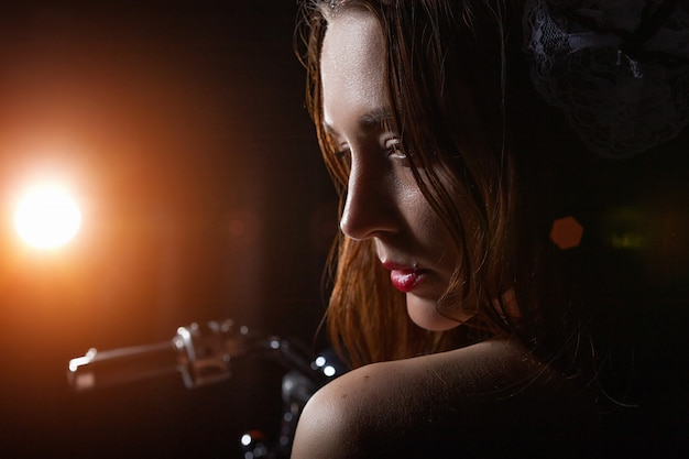 Portrait of a girl who sits on a motorcycle in a dark room shines a lantern