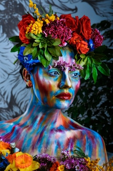 Portrait of a girl whose face is painted with colored paints in a wreath of flowers. in frida kahlo's footsteps