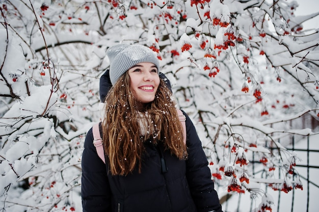Portrait of girl at winter snowy day near snow covered trees.