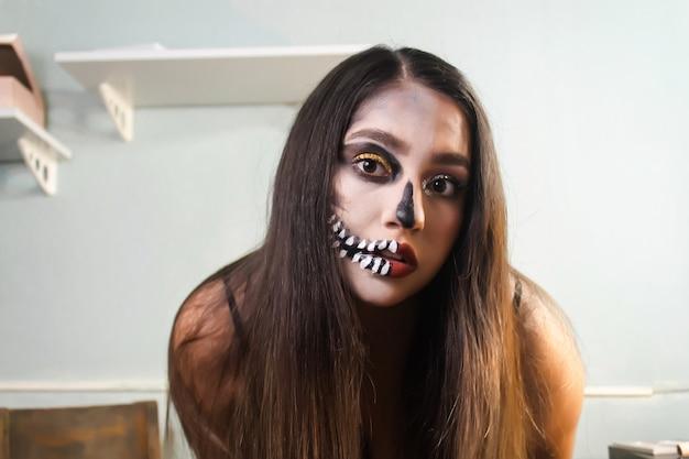 Portrait of a girl with artistic skull makeup. halloween makeup
