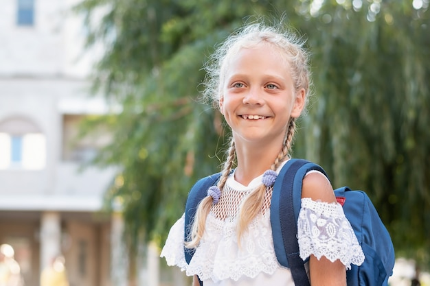 Portrait of a girl with a backpack near the school