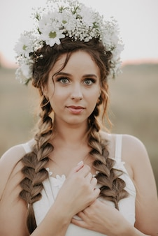 Portrait of a girl with braids and a floral wreath in a white boho dress in summer outdoors