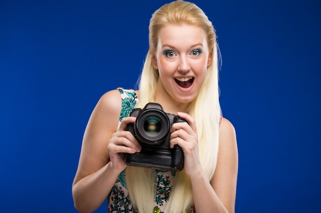 Portrait of a girl with a camera in hands